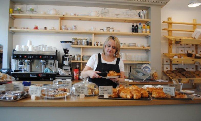 Izabela Szypulska, café assistant, serves a croissant