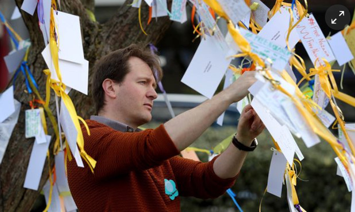 Richard Ratcliffe adding another card for his wife to the tree on Fortune Green Photograph: Gareth Fuller PA